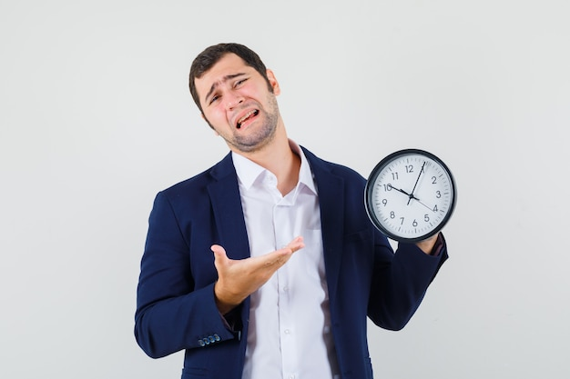 Young male in shirt and jacket showing wall clock and looking wistful