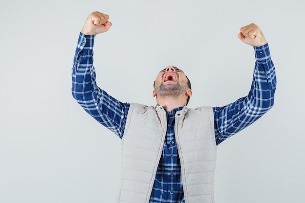 Giovane maschio in camicia, giacca che mostra il gesto del vincitore e che sembra grato, vista frontale.