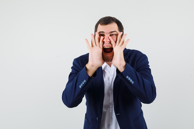 Young male in shirt and jacket telling secret or shouting