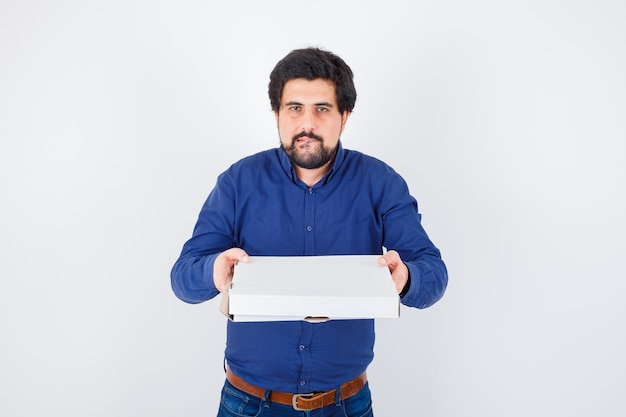 Young male in shirt, jeans holding closed pizza box and looking hungry , front view.