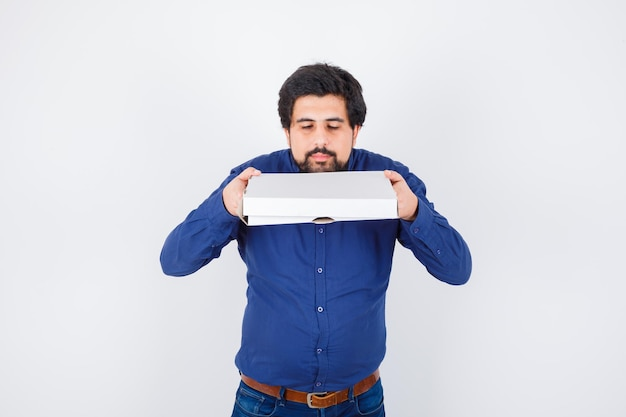 Young male in shirt, jeans holding closed pizza box and looking pretty , front view.