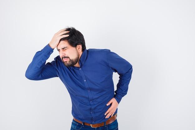 Giovane maschio in camicia, jeans tenendo la mano sulla testa e guardando male, vista frontale.