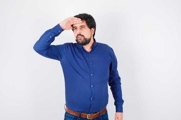Giovane maschio in camicia, jeans che guarda lontano mentre tiene la mano sulla fronte e sembra sicuro, vista frontale.