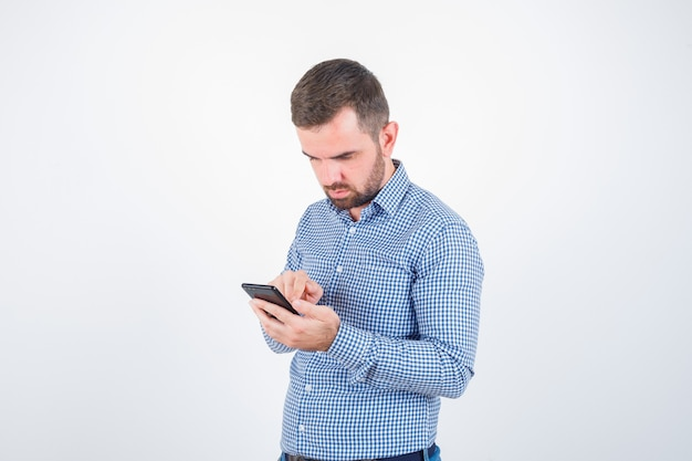Giovane maschio in camicia, jeans guardando il cellulare e guardando serio, vista frontale.