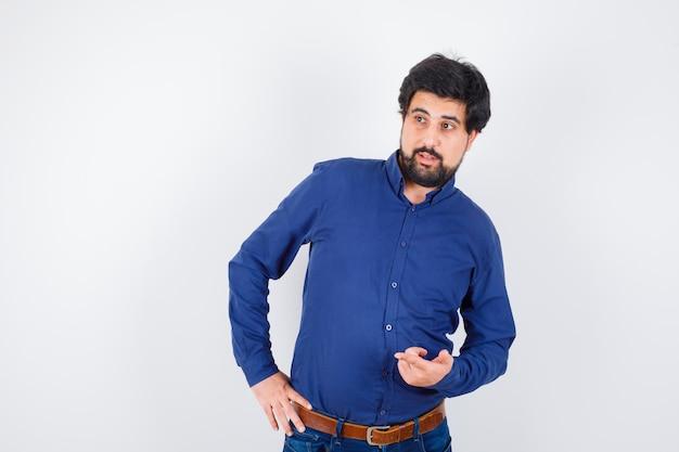 Giovane maschio in camicia, jeans che punta da parte mentre si tiene la mano sulla vita e sembra gioiosa, vista frontale.