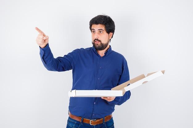 Giovane maschio in camicia, jeans che puntano lontano mentre tiene in mano una scatola della pizza e sembra sorpreso, vista frontale.