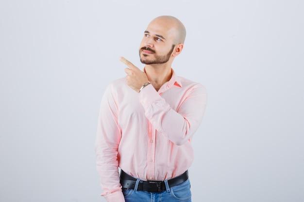Giovane maschio in camicia, jeans che punta all'angolo in alto a sinistra e sembra fiducioso, vista frontale.