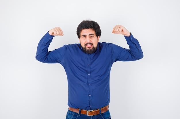 Giovane maschio in camicia, jeans che mostra i muscoli delle braccia e sembra stressato.