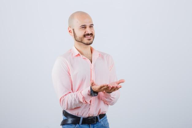Giovane maschio in camicia, jeans che allungano le mani a coppa e sembrano pacifici, vista frontale.