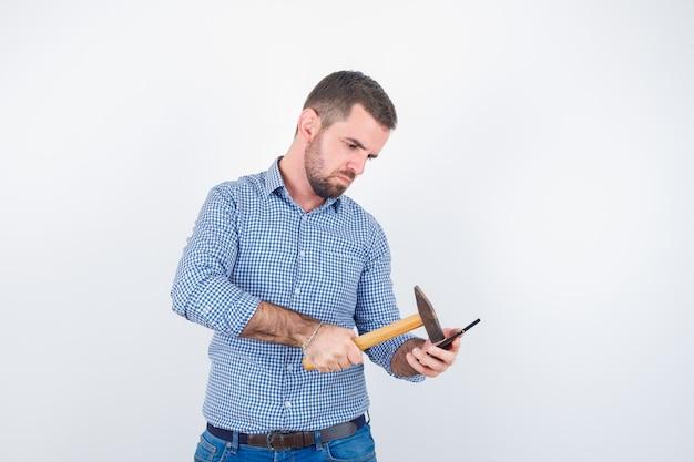 Giovane maschio in camicia, jeans che colpisce il telefono cellulare con un martello e che sembra serio, vista frontale.