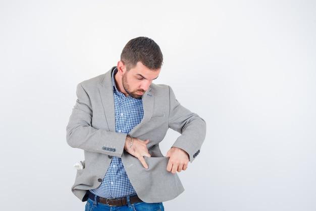 Giovane maschio in camicia, jeans, giacca del vestito guardando la tasca della giacca e guardando curioso, vista frontale.