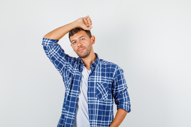 Young male in shirt leaning head on raised arm and looking cute , front view.