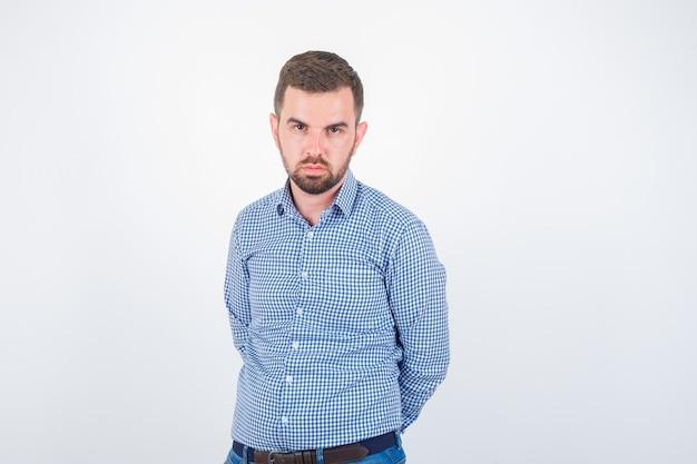 Giovane maschio in camicia che guarda l'obbiettivo e guardando serio, vista frontale.