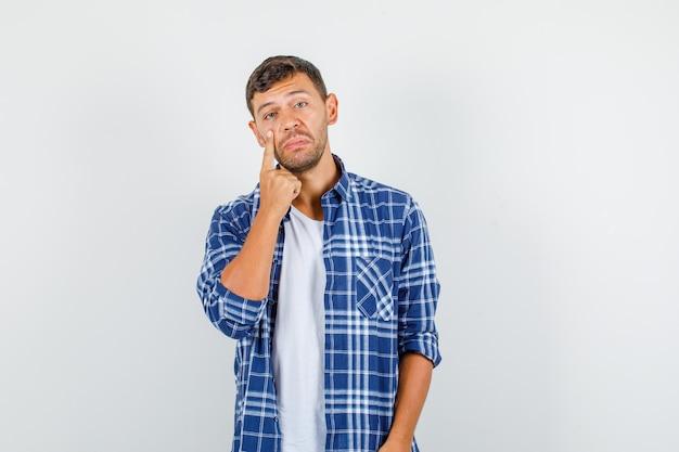 Giovane maschio in camicia tirando giù la palpebra e guardando triste, vista frontale.