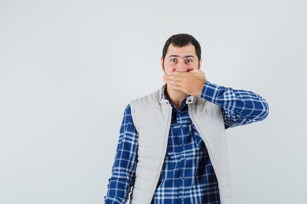 Giovane maschio in camicia, giacca senza maniche tenendo le mani sulla bocca e guardando calmo, vista frontale.