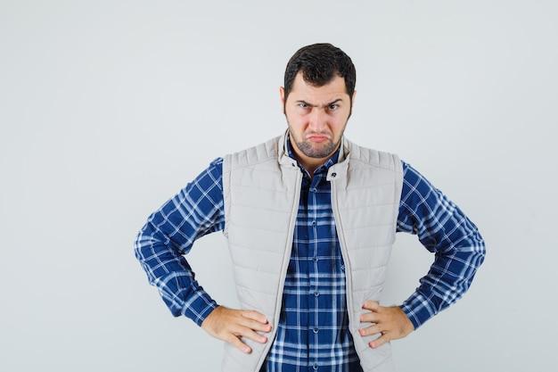 Giovane maschio in camicia, giacca senza maniche tenendo le mani sulla sua vita e guardando arrabbiato, vista frontale.