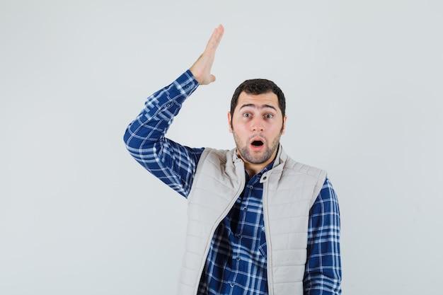 Giovane maschio in camicia, giacca senza maniche alzando la mano e guardando stupito, vista frontale.