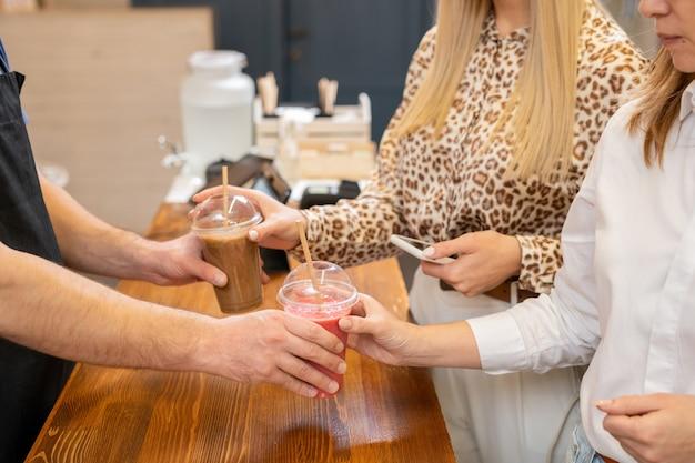 Молодой продавец-мужчина передает два молочных коктейля или коктейля в пластиковых стаканах покупателям-женщинам через прилавок в кафетерии