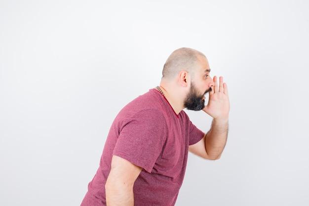 ピンクのtシャツを着て誰かを叫び、エネルギッシュに見える若い男性。 。