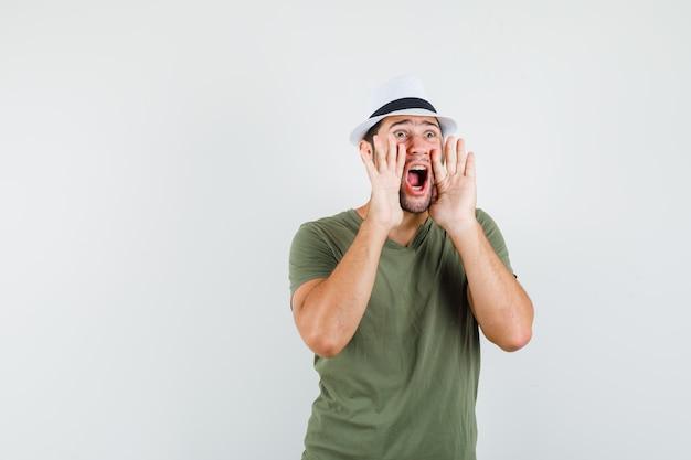 緑のtシャツと帽子の正面図で何かを叫んだり発表したりする若い男性。