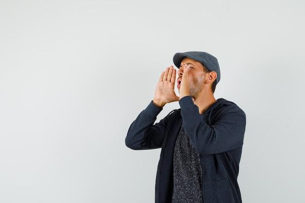 젊은 남성 소리 또는 t- 셔츠, 재킷, 모자 전면보기에서 뭔가 발표.