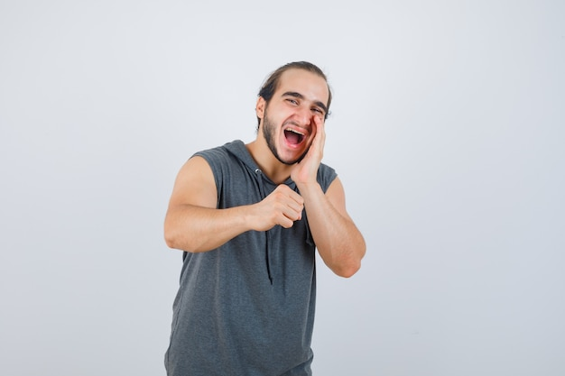 Young male shouting something while raising clenched fist in sleeveless hoodie and looking happy , front view.