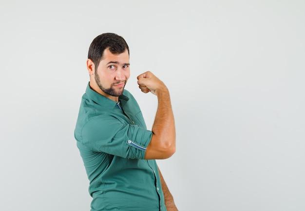 Молодой мужчина показывает мышцы руки в зеленой рубашке и выглядит красивым, вид спереди.