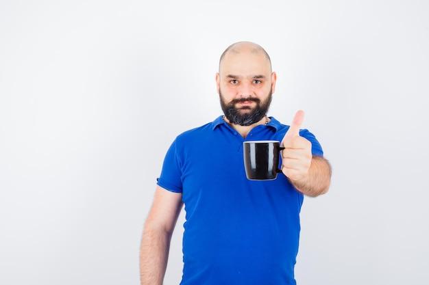 Молодой самец показывает черную чашку к камере в вид спереди голубой рубашке.