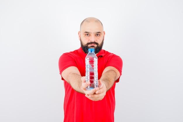 Giovane maschio che mostra la bottiglia alla telecamera in camicia rossa e sembra sicuro. vista frontale.