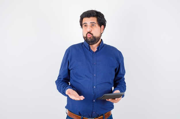 Young male showing calculator while discussing in royal blue shirt , front view.