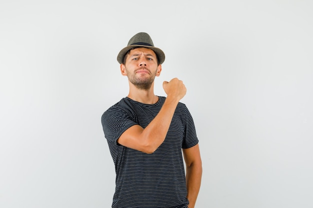 Young male showing clenched fist in t-shirt hat and looking confident