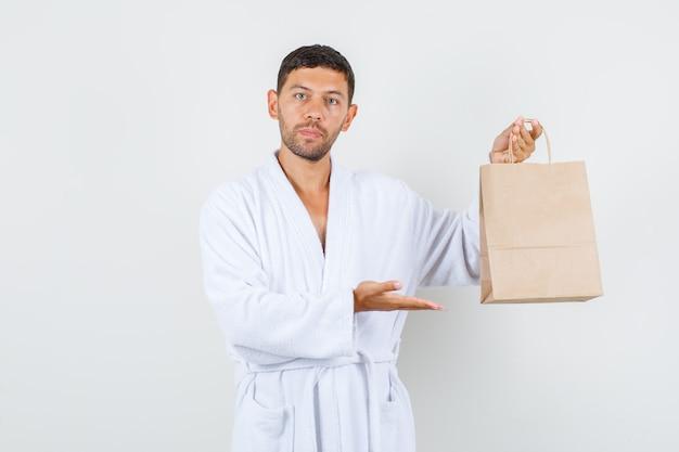 Молодой мужчина показывает бумажный мешок ремесла в белом халате и выглядит строго. передний план.