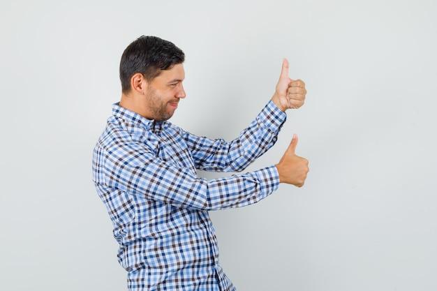Giovane maschio che mostra i doppi pollici in su in camicia controllata e che sembra soddisfatto.