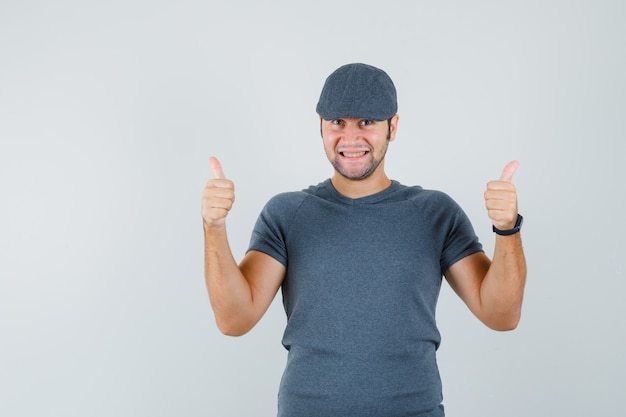 Young male showing double thumbs up in grey t-shirt cap and looking joyful