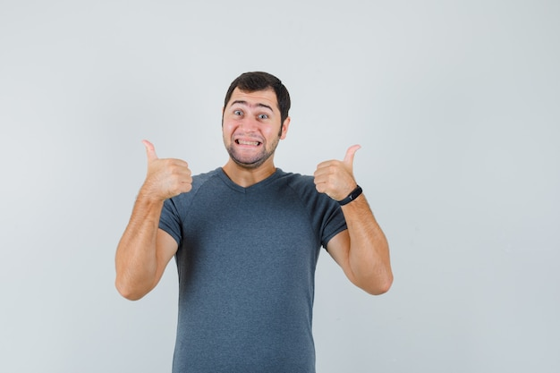 Young male showing double thumbs up in grey t-shirt and looking merry