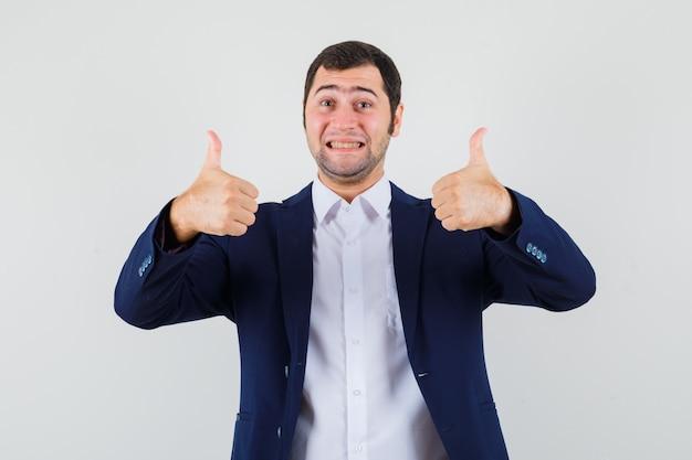 シャツとジャケットで二重の親指を示し、幸せそうに見える若い男性