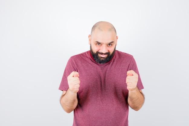 분홍색 티셔츠에 무화과 제스처를 보여주는 젊은 남성, 전면 보기.