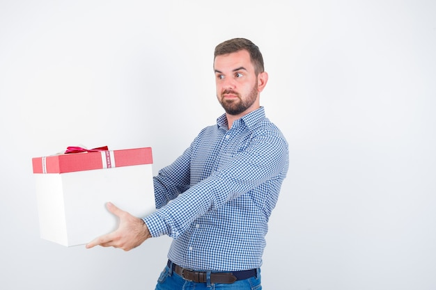 Молодой мужчина показывает жест, держа подарочную коробку в рубашке, джинсах и выглядит уверенно, вид спереди.