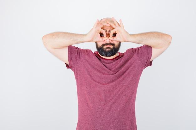 Молодой мужчина показывает жест в очках в розовой футболке.