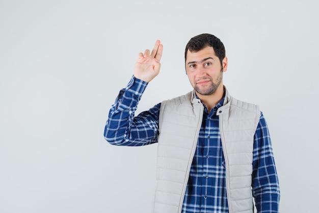 셔츠, 민소매 재킷에 작별 제스처를 보여주는 젊은 남성 기쁘게, 전면보기를 찾고.
