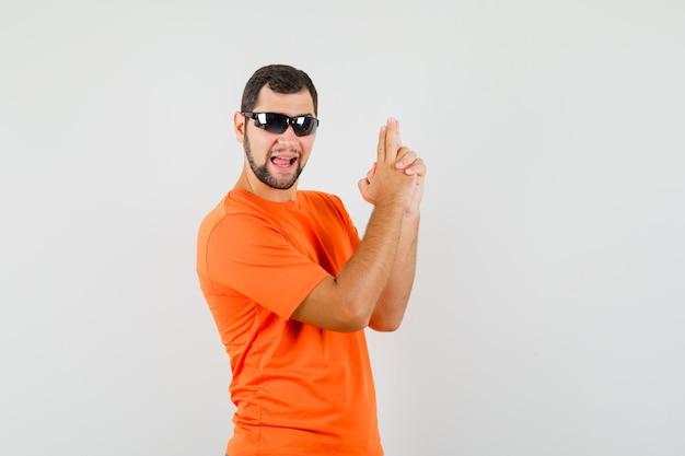 オレンジ色のtシャツで銃のジェスチャーを示し、自信を持って見える若い男性。正面図。
