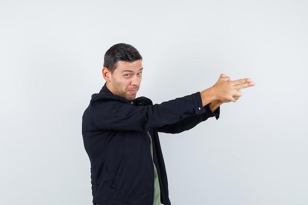 Tシャツ、ジャケットで銃のジェスチャーを示し、イライラしているように見える若い男性。正面図。