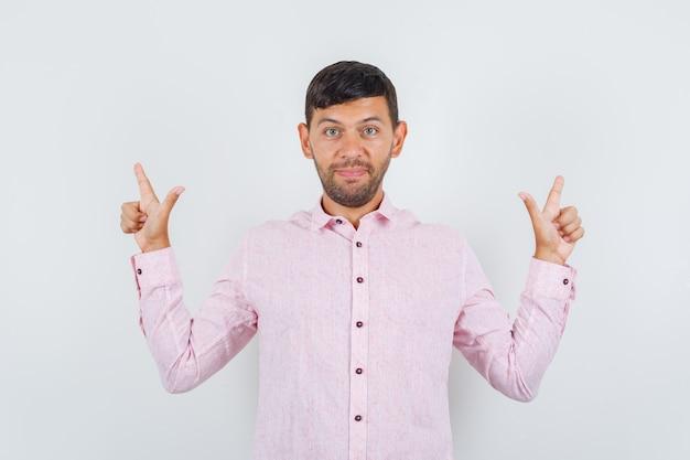 Giovane maschio che mostra il gesto della pistola in camicia rosa e guardando allegro, vista frontale.