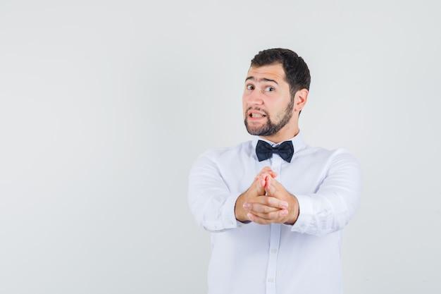 銃のジェスチャーを示す若い男性は、白いシャツを着てカメラを指さし、自信を持って見えます。正面図。
