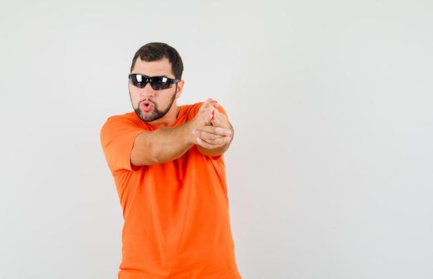 Молодой мужчина показывает жест пистолета в оранжевой футболке и выглядит уверенно, вид спереди.