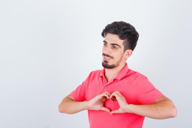 ピンクのtシャツでハートのジェスチャーを示し、自信を持って見える若い男性。正面図。