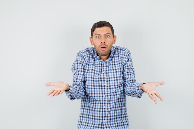Giovane maschio che mostra gesto impotente alzando le spalle in camicia a quadri e guardando confuso