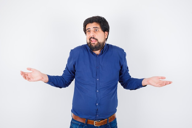 Giovane maschio che mostra gesto impotente scrollando le spalle in camicia, jeans e guardando confuso.