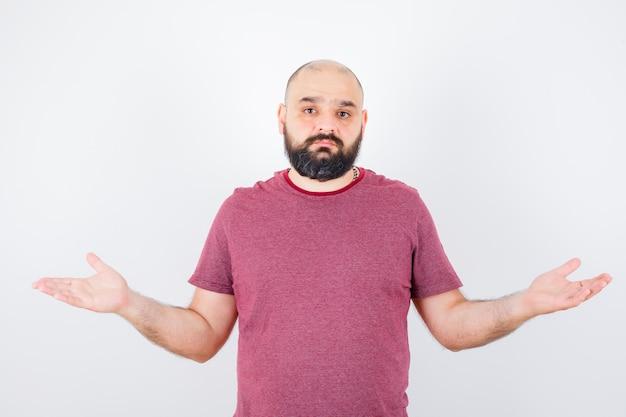 분홍색 티셔츠에 무력한 몸짓을 보이고 불쾌해 보이는 젊은 남성. 전면보기.