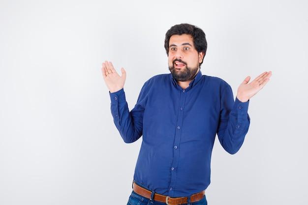 ロイヤルブルーのシャツの正面図で無力なジェスチャーを示す若い男性。